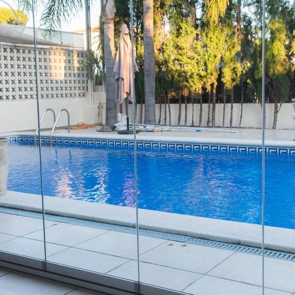 cerramientos de porche enfrente de piscina hecho con cortina de cristales transparentes sin perfiles
