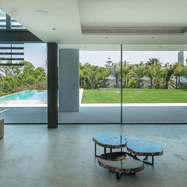 Ventana corredera minimalista en salon con vistas a jardin y a piscina de alurei.com