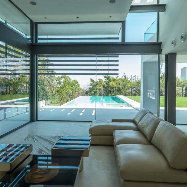 ventana corredera minimalista en salon con vista a piscina en casa de lujo de alurei.com
