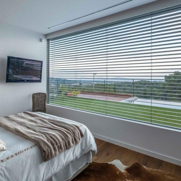 ventana minimalista con persiana de lama orientable, con vistas a jardin